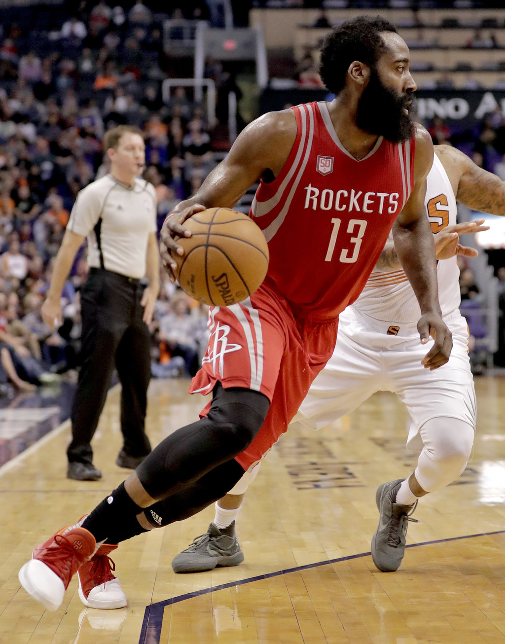 Houston Rockets guard James Harden (13) drives against the Phoenix Suns during the first half of an NBA basketball game, Wednesday, Dec...