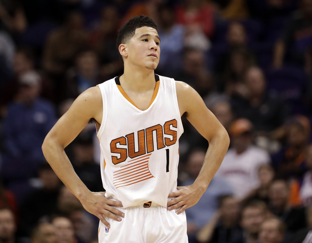 Phoenix Suns guard Devin Booker pauses during a stop in play in the second half of the team's NBA basketball game against the Houston R...