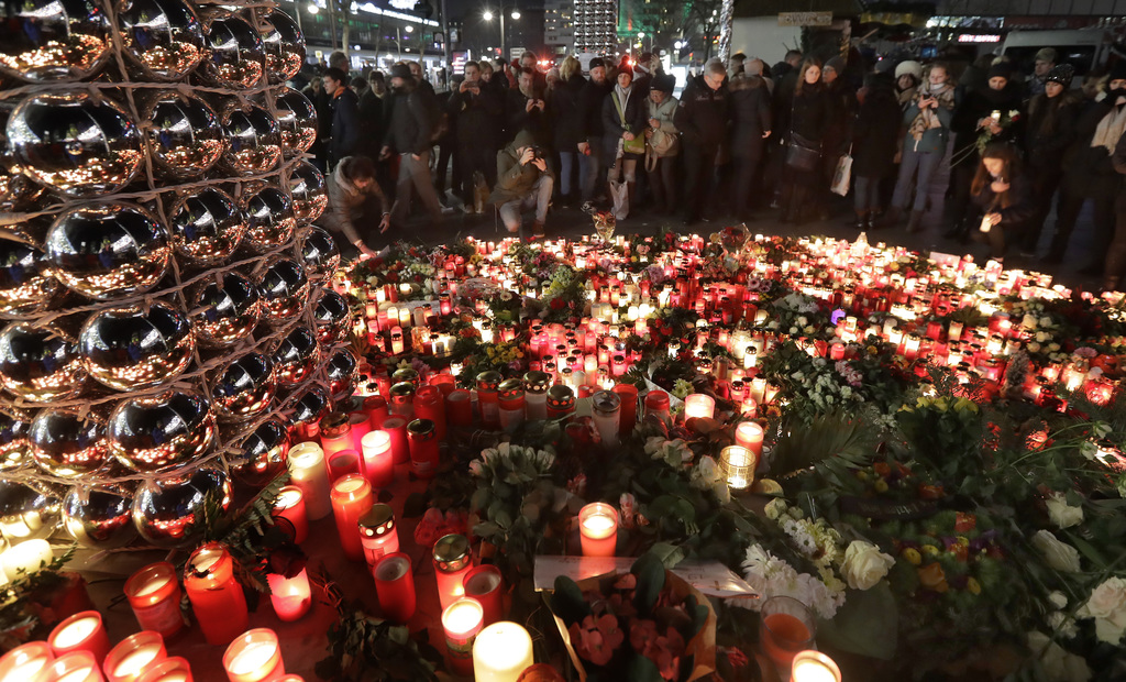People stay in front of candles close to a Christmas market beside the memorial church in Berlin, Germany, Wednesday, Dec. 21, 2016, tw...