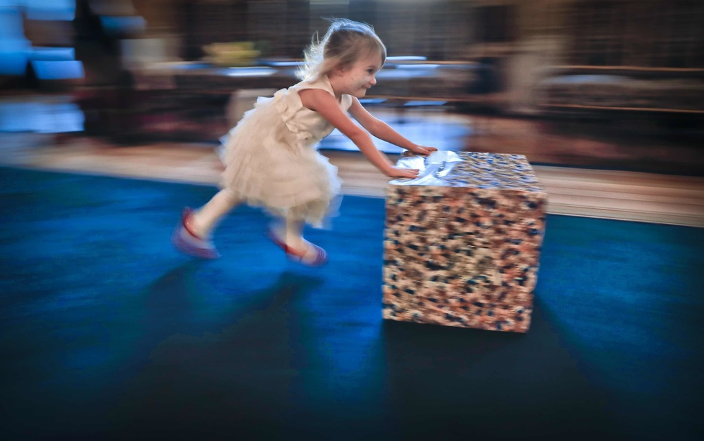 In this Tuesday, Dec. 13, 2016 photo taken with a slow shutter speed, 3 year old Nicole pushes her present box, after a Christmas show ...