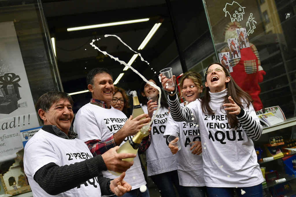 Agustin Moreno, left, owner of a lottery office, celebrates with his staff after selling the second prize Christmas lottery ticket ''El...