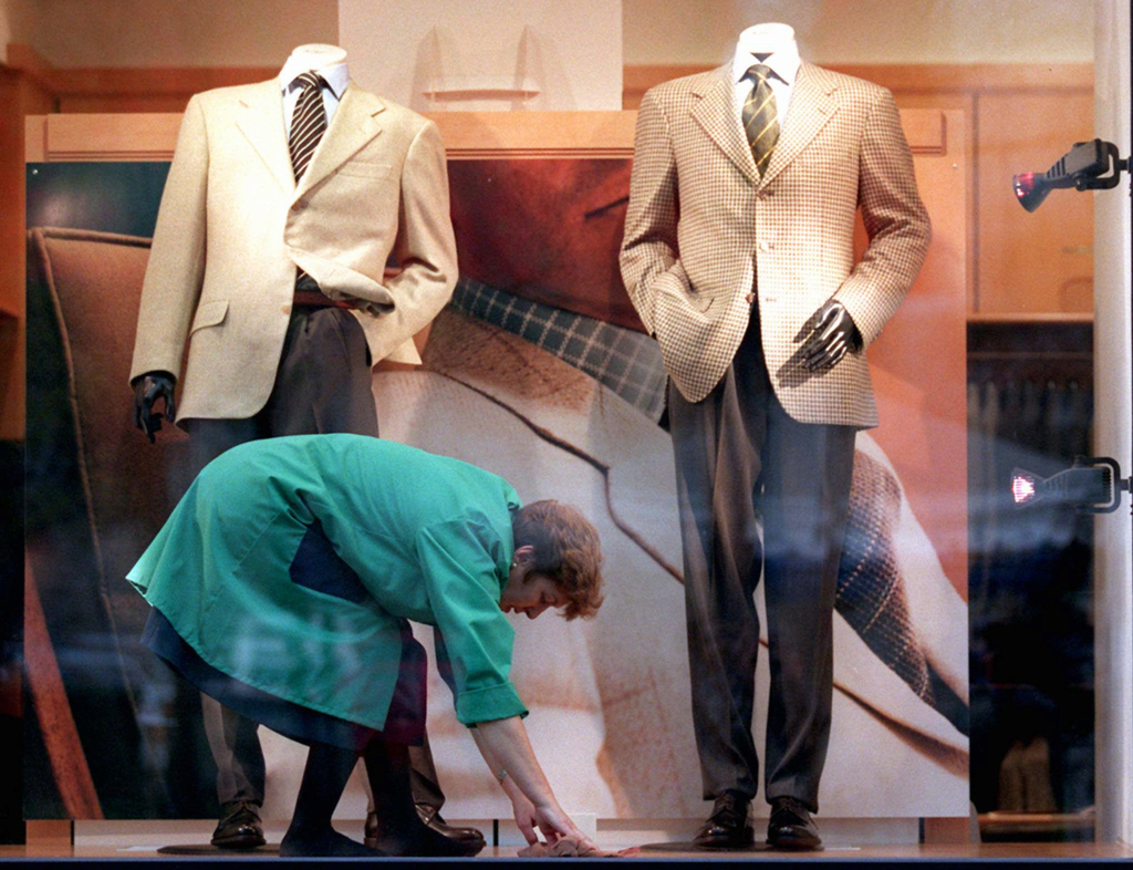 FILE - In this Monday Oct. 21, 1996, a woman cleans a window display under the watchful eye of two casual, headless mannequins displayi...