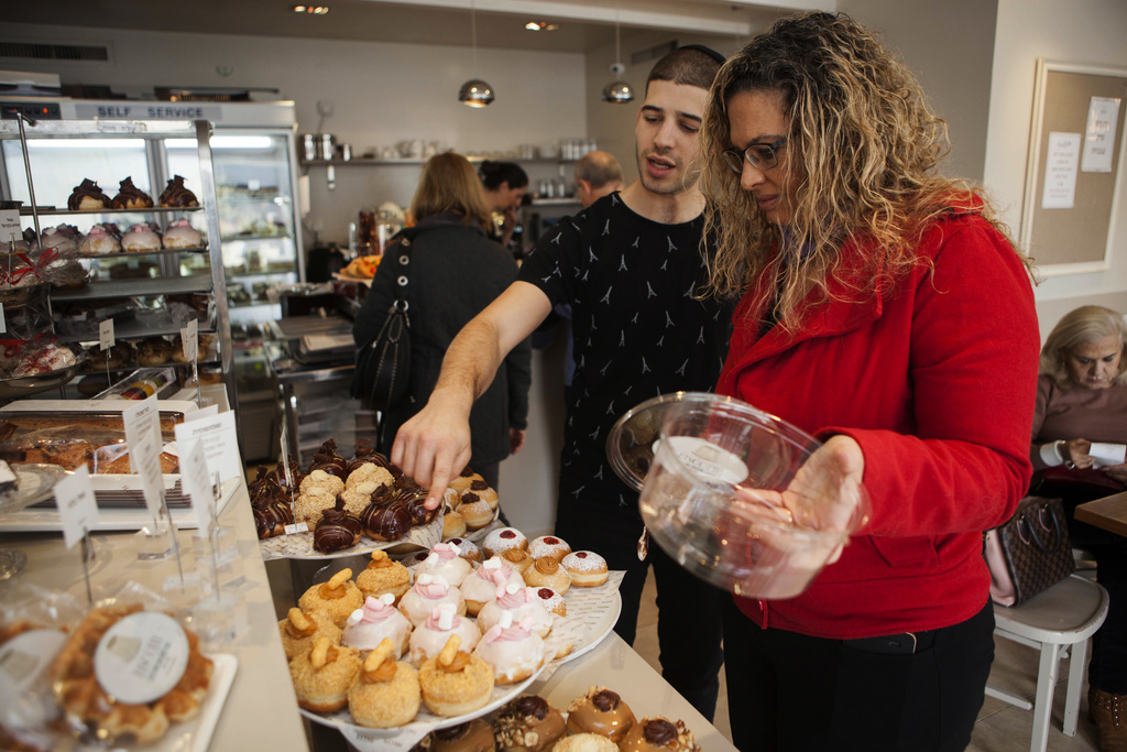 In this Thursday, Dec. 15, 2016 photo, a bakery employee helps customer choose doughnuts in Bnei Brak, Israel. Israelis are finding new...