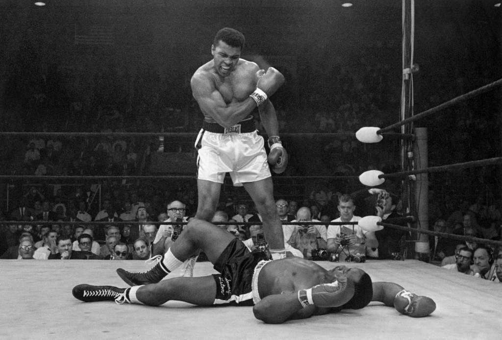 FILE - In this May 25, 1965, file photo, heavyweight champion Muhammad Ali stands over fallen challenger Sonny Liston, shouting and ges...