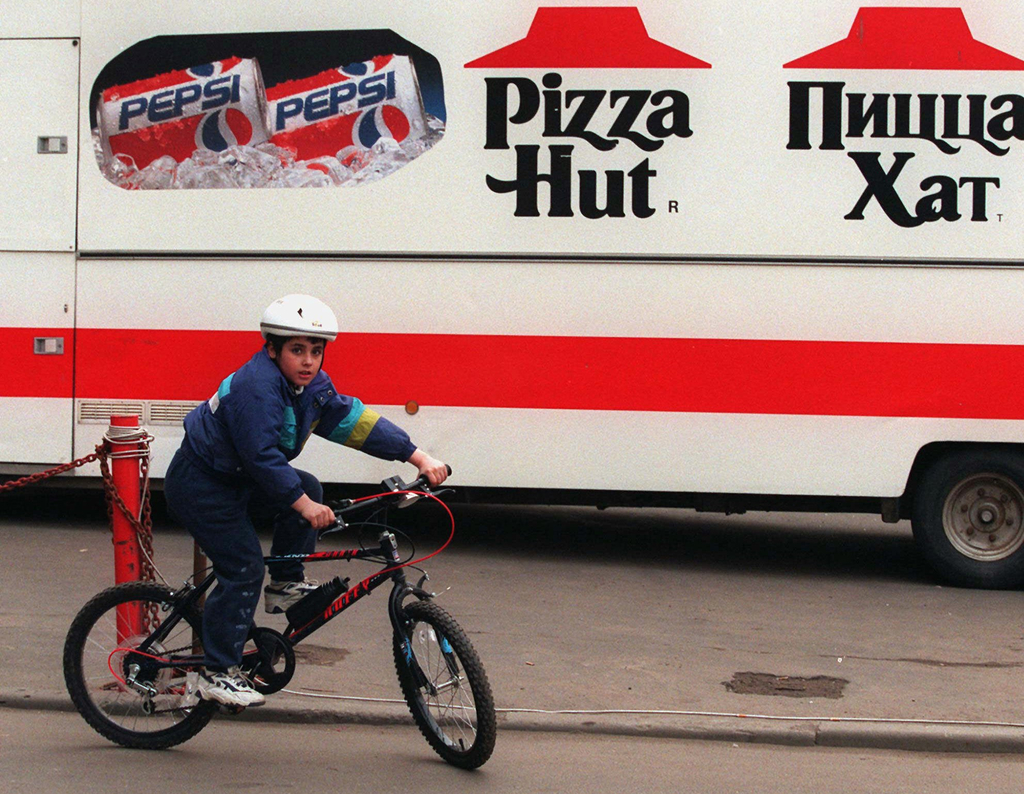 FILE - In this Wednesday, April 23, 1997 file photo, a boy rides his bike past a Pizza Hut van in Moscow. AP's Nataliya Vasilyeva, who ...