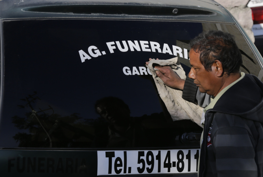 A funeral home driver washes the hearse as he waits to transport a body from the funeral home in Tlalnepantla, a municipality near the ...