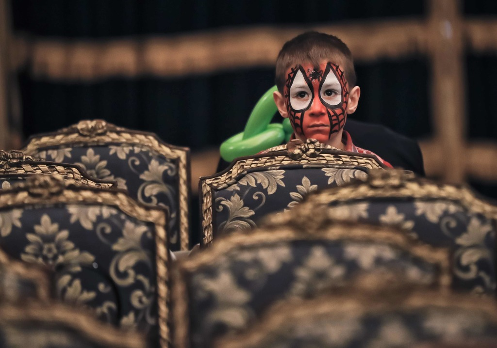 In this Tuesday, Dec. 13, 2016 photo, a boy, his face painted with a Spiderman mask, stands behind chairs during a Christmas show for c...
