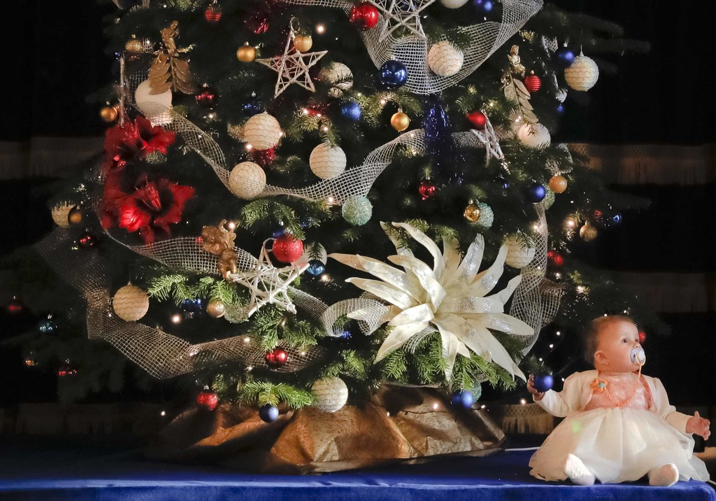 In this Tuesday, Dec. 13, 2016, picture, a baby is placed next to a Christmas tree after a Christmas show for children of Romanian mili...