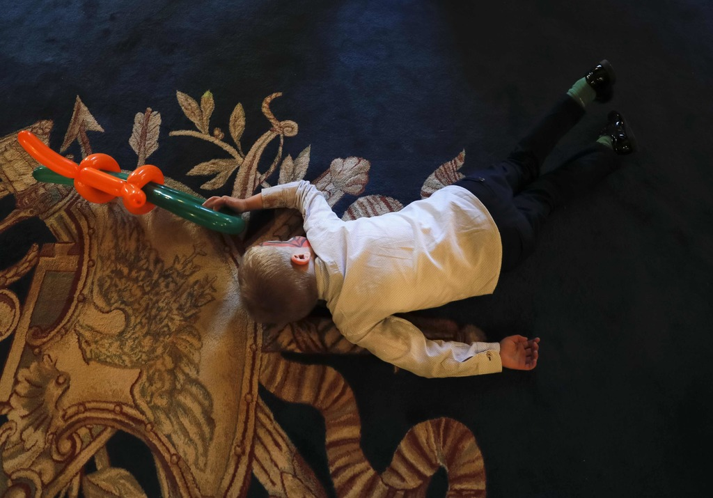 In this Tuesday, Dec. 13, 2016 photo, a boy lays on the floor and holds balloons shaped to resemble a weapon while playing with other c...