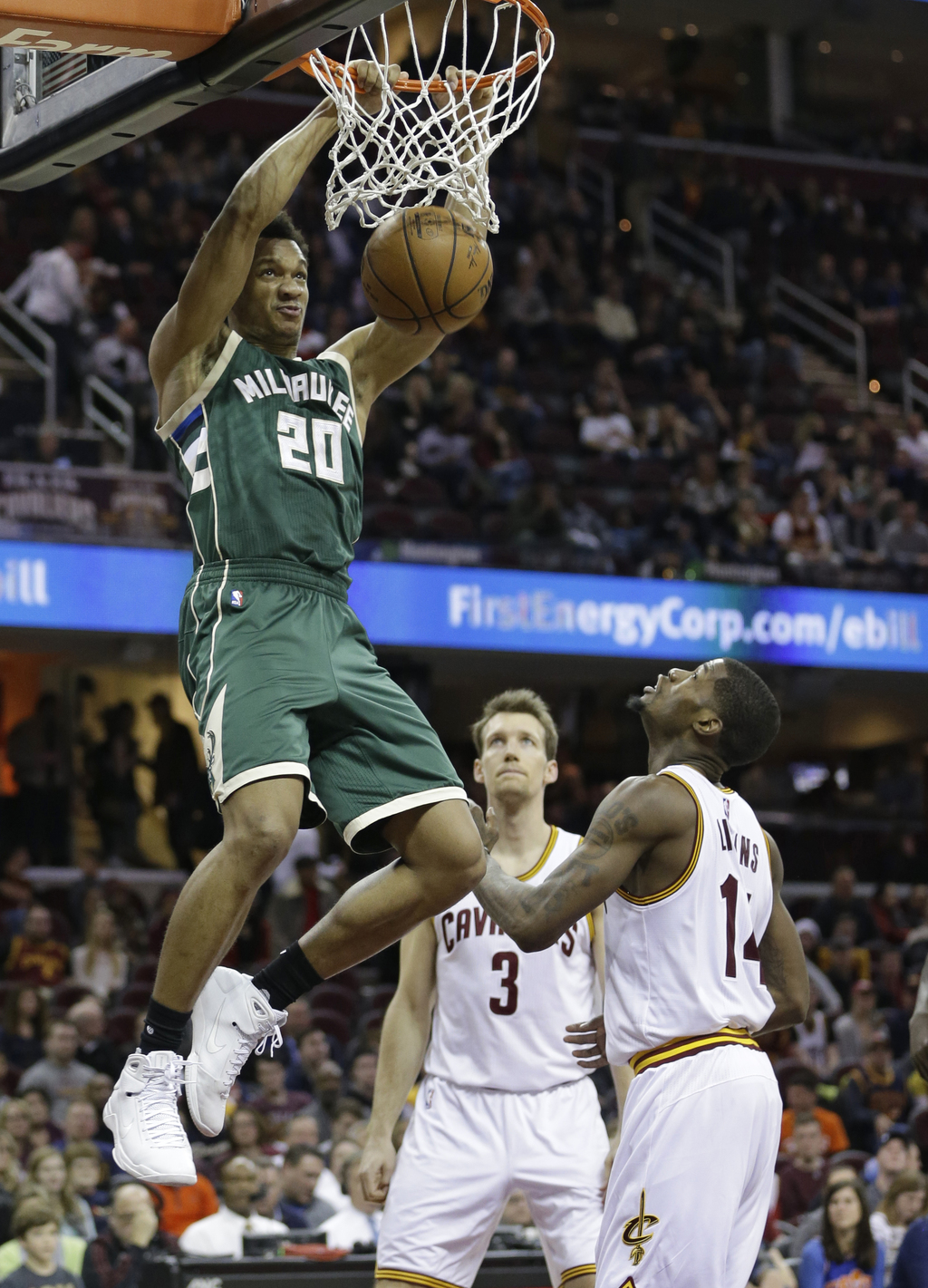 Milwaukee Bucks' Rashad Vaughn (20) dunks against Cleveland Cavaliers' DeAndre Liggins, right, and Mike Dunleavy during the second half...