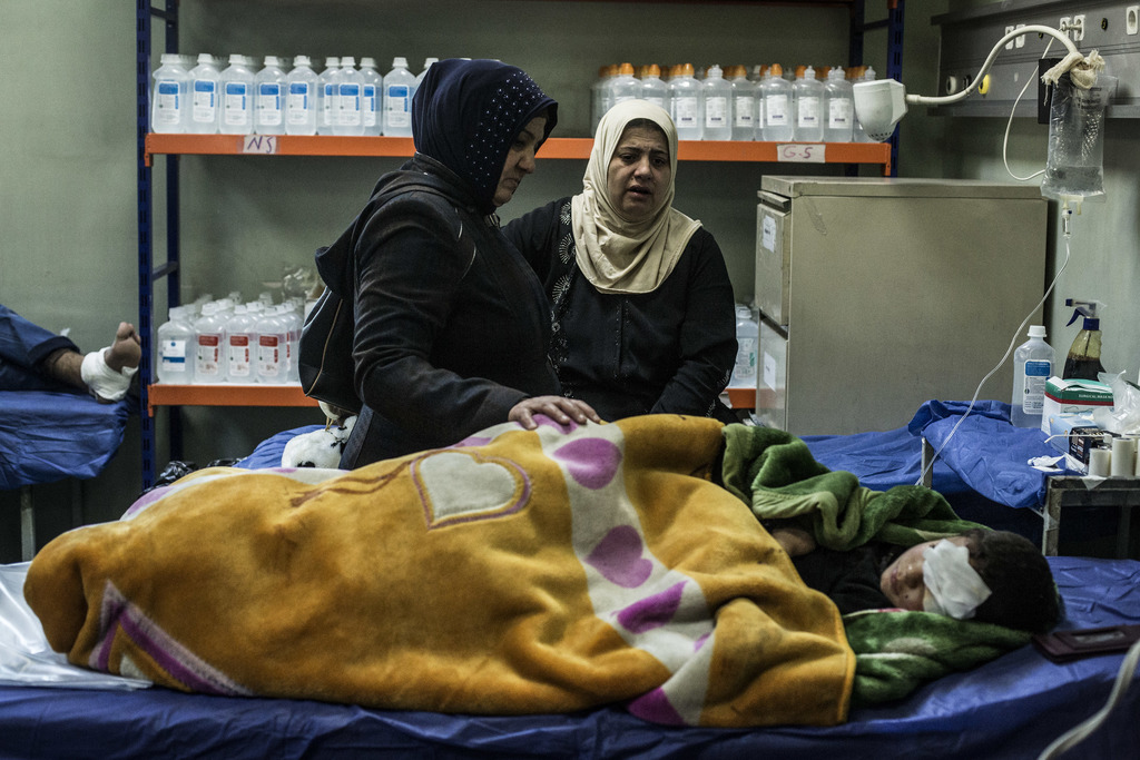 The mother and aunt of a boy wounded in a car bomb attack in the district of Gogjali in Mosul comfort him in a hospital in Irbil, Iraq,...