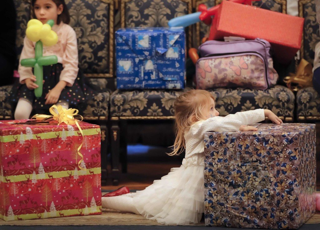 In this Tuesday, Dec. 13, 2016 photo, 3 year old Nicole holds on to her present during a Christmas show for children of Romanian milita...