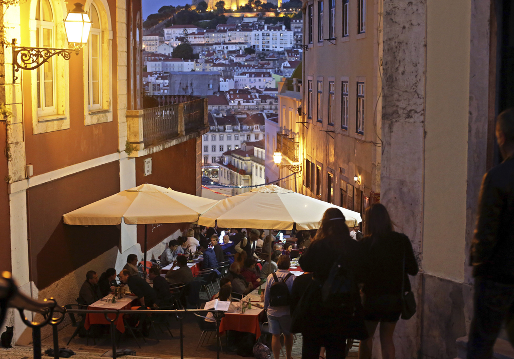 FILE - In this May 25, 2016 file photo, tourists have dinner at restaurant tables set outside with a view of Saint George castle in the...