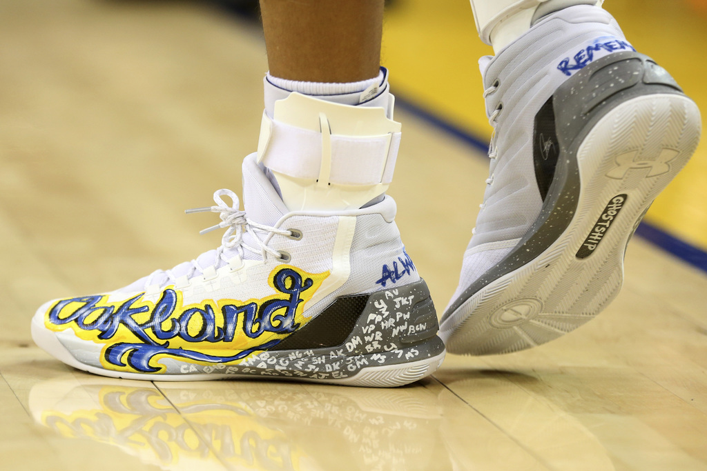 This Dec. 15, 2016 photo shows the shoes worn by Golden State Warriors' Stephen Curry that honor victims of a warehouse fire during an ...
