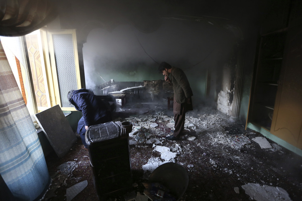 Afghan men inspect the remains of their belongings at a parliament member's house in the aftermath of gunmen attack at last night in we...