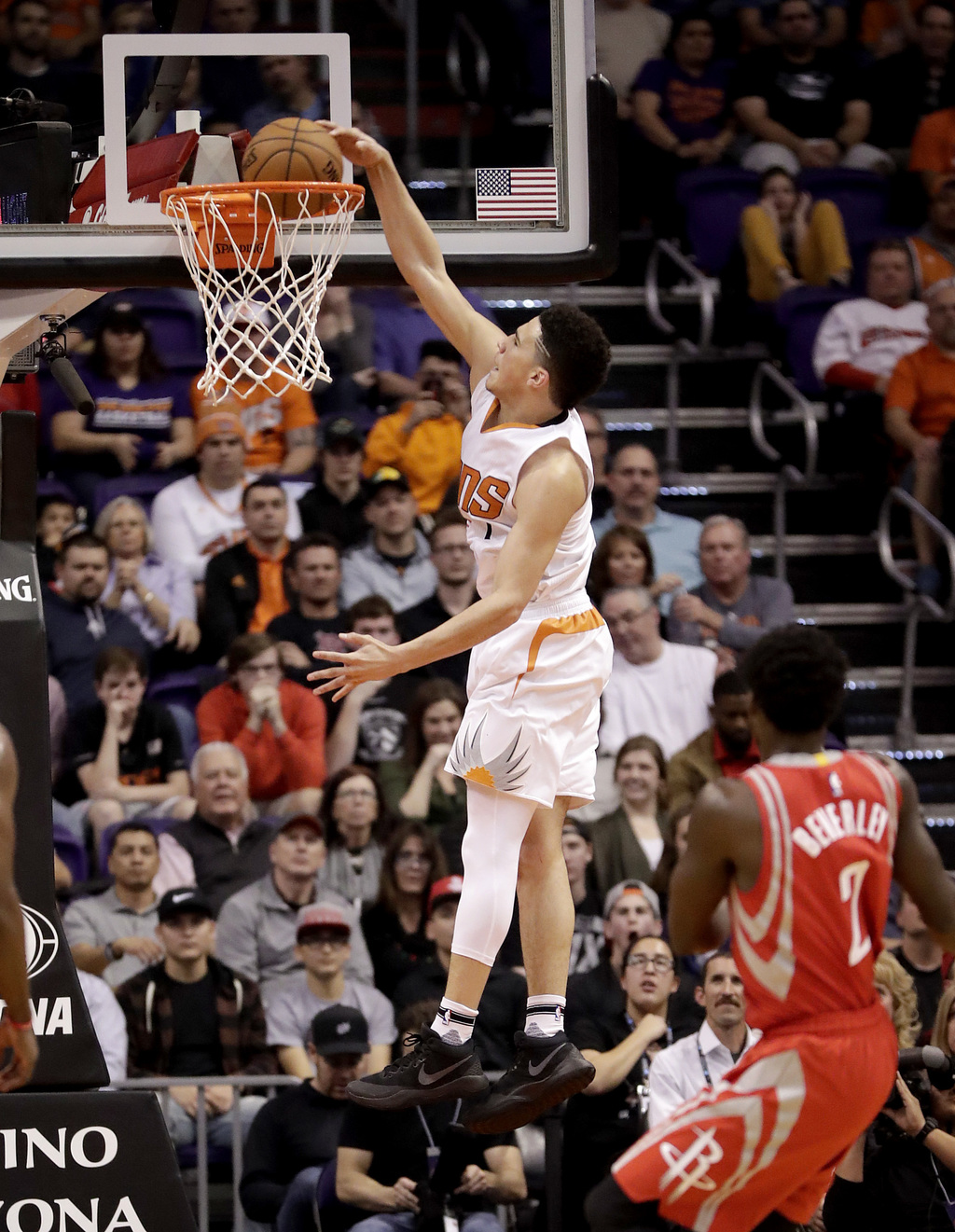 Phoenix Suns guard Devin Booker (1) dunks as Houston Rockets guard Patrick Beverley (2) watches during the first half of an NBA basketb...