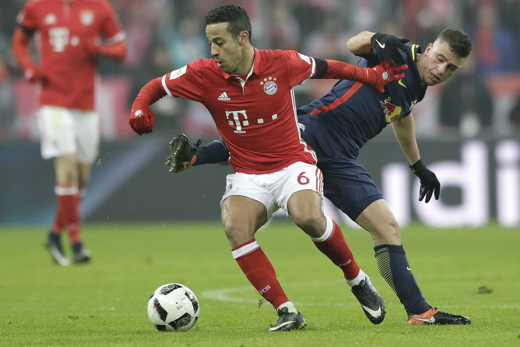 Bayern's Thiago, left, and Leipzig's Diego Demme challenge for the ball during the German Bundesliga soccer match between FC Bayern Mun...