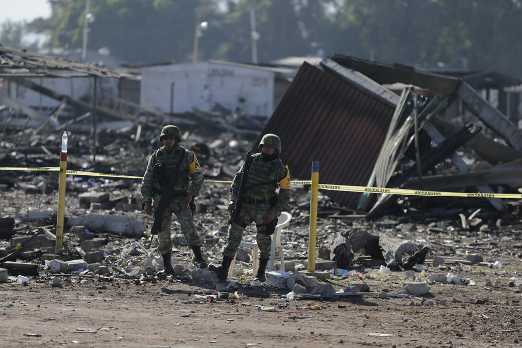 Soldiers stand guard at the open-air San Pablito fireworks market that exploded in Tultepec on the outskirts of Mexico City, Wednesday,...
