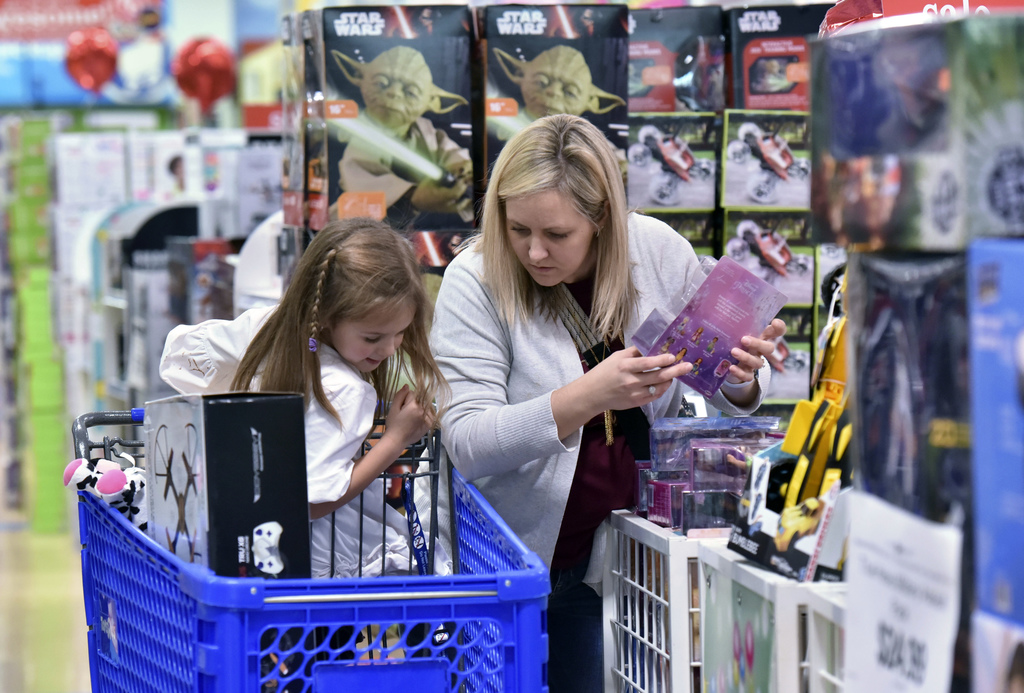 FILE - In this Thursday, Nov. 24, 2016, file photo, Stephanie Rowell and her daughter Sydney, 5, shop at Toys R Us - Town Center in Ken...