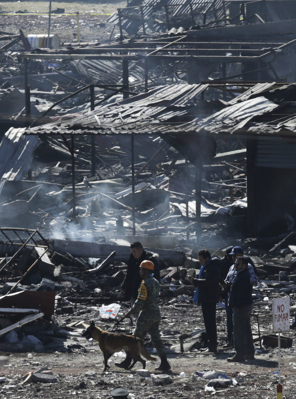 Soldiers and investigators walk through the scorched rubble of the open-air San Pablito fireworks market that exploded in Tultepec on t...