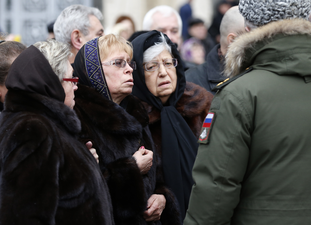 Marina Karlova, second left, a widow of killed Russian ambassador to Turkey, Andrei Karlov, and his mother Maria, third left, stand out...