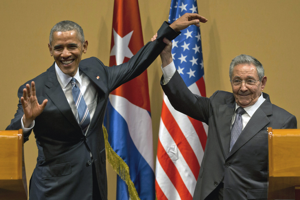 FILE - In this March 21, 2016, file photo, Cuban President Raul Castro, right, lifts up the arm of President Barack Obama at the conclu...