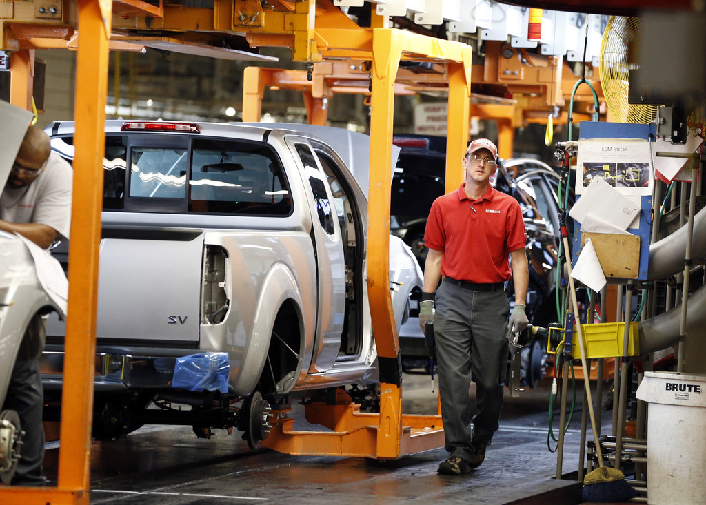 In this April 6, 2016, photograph, a technician walks past vehicles on the assembly line at the Nissan Canton Vehicle Assembly Plant in...