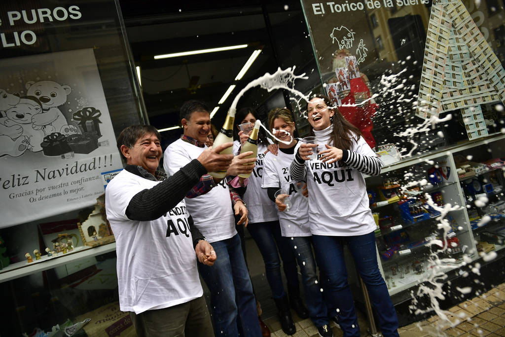 Agustin Moreno, owner of a lottery office, celebrates with his staff after selling the second prize Christmas lottery ticket ''El Gordo...