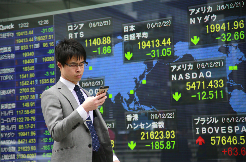 A man uses a mobile phone in front of an electronic stock indicator of a securities firm in Tokyo, Thursday, Dec. 22, 2016. Shares were...