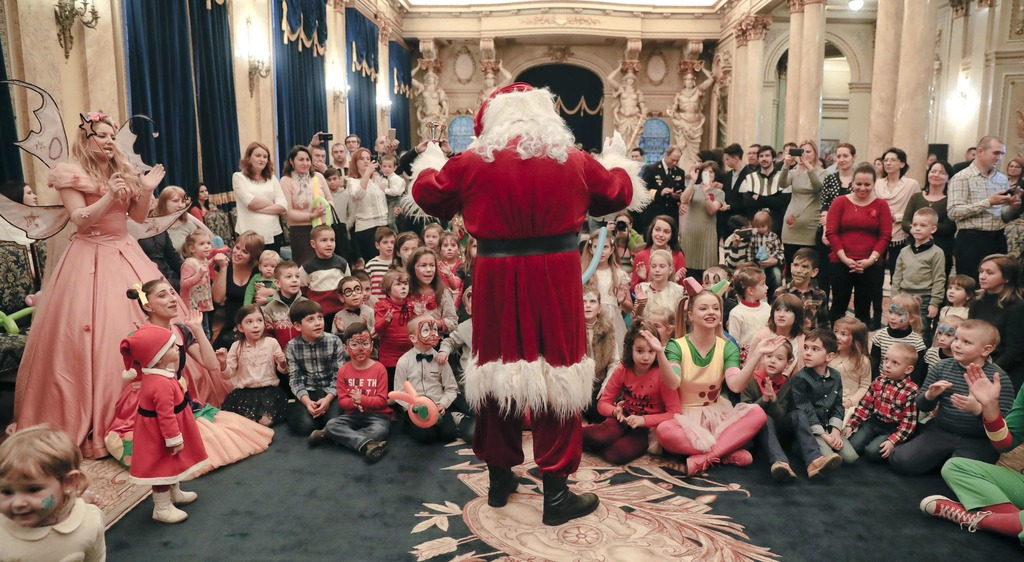 In this Tuesday, Dec. 13, 2016 photo, a man wearing a Santa Claus outfit speaks to children of Romanian military families during a Chri...