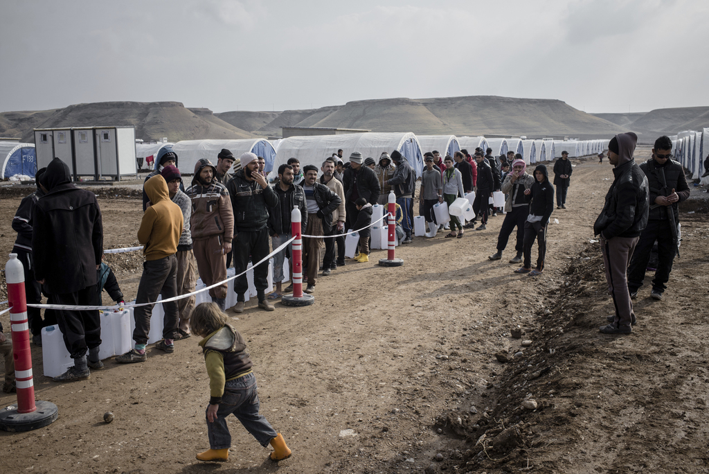 Men wait in line for fuel distributions at Sewdinan Camp for the displaced near Khazer, Iraq on Wednesday, Dec. 21, 2016. Human Rights ...