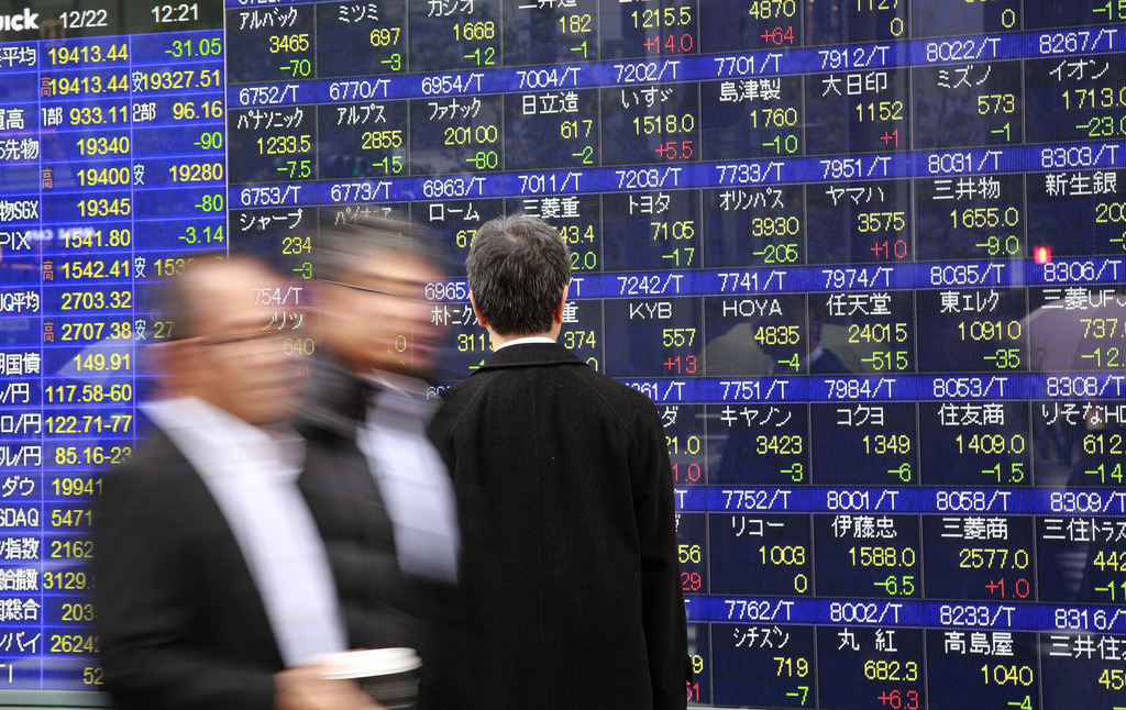 A man looks at an electronic stock indicator of a securities firm in Tokyo, Thursday, Dec. 22, 2016. Shares were meandering in thin tra...