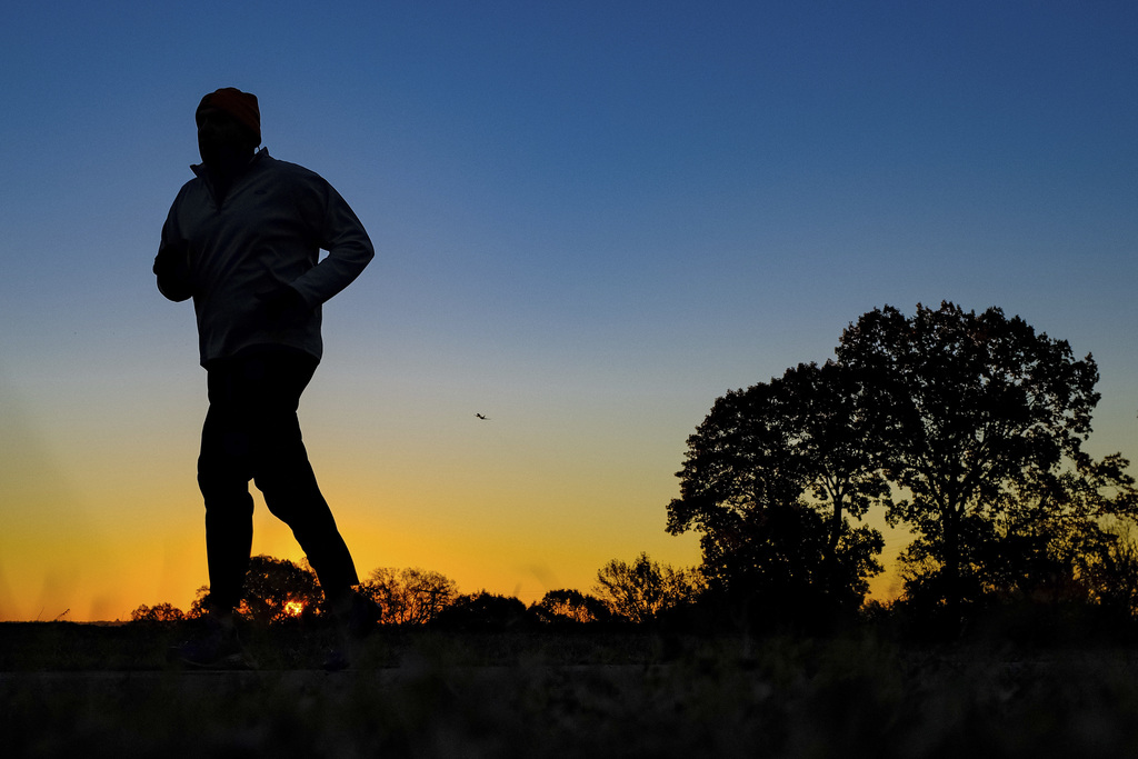 FILE - In this Tuesday, Nov. 22, 2016, file photo, a runner is silhouetted against the sunrise on his early morning workout near Arling...