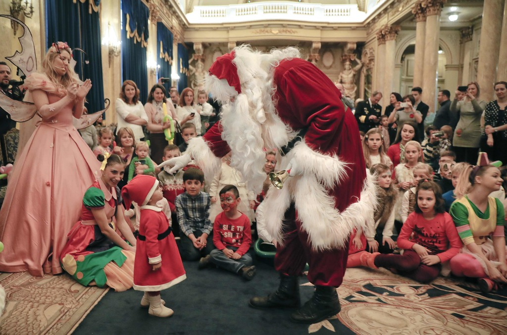In this Tuesday, Dec. 13, 2016 photo, a man wearing a Santa Claus outfit speaks to 19 month old Maya during a Christmas show for childr...