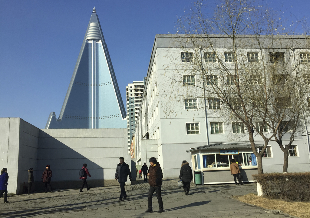 In this Dec. 11, 2016 photo, residents pass by the towering Ryugyong Hotel in Pyongyang, North Korea. Thirty years after work began on ...