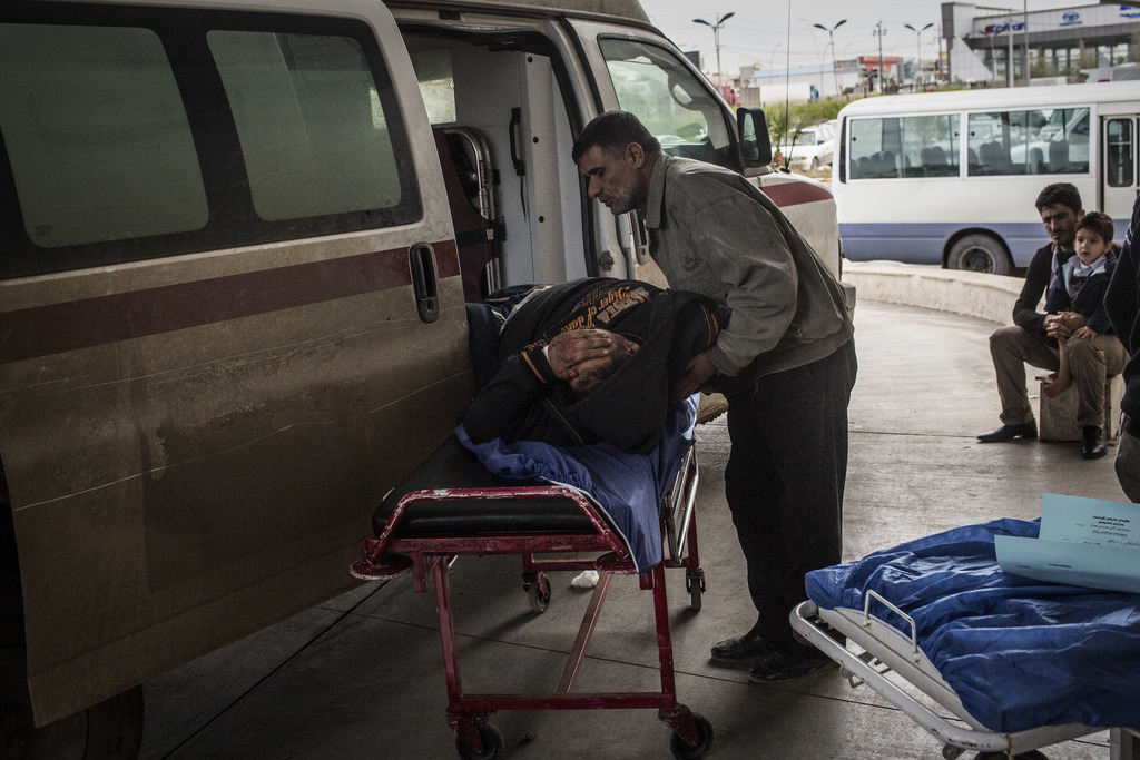 A Iraqi man wounded in a car bomb attack in the liberated district of Gogjali arrives to a hospital in Irbil, Iraq, Thursday, Dec. 22, ...