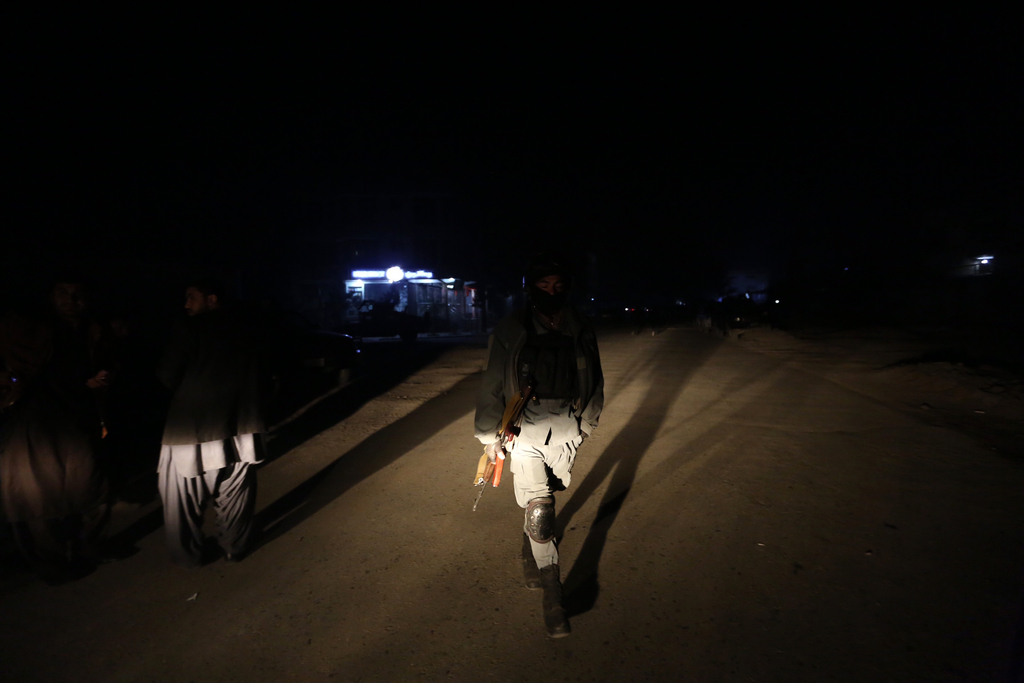 An Afghan policeman patrols the site of attack on an Afghan parliament member's house in western Kabul, Afghanistan, Wednesday, Dec. 21...