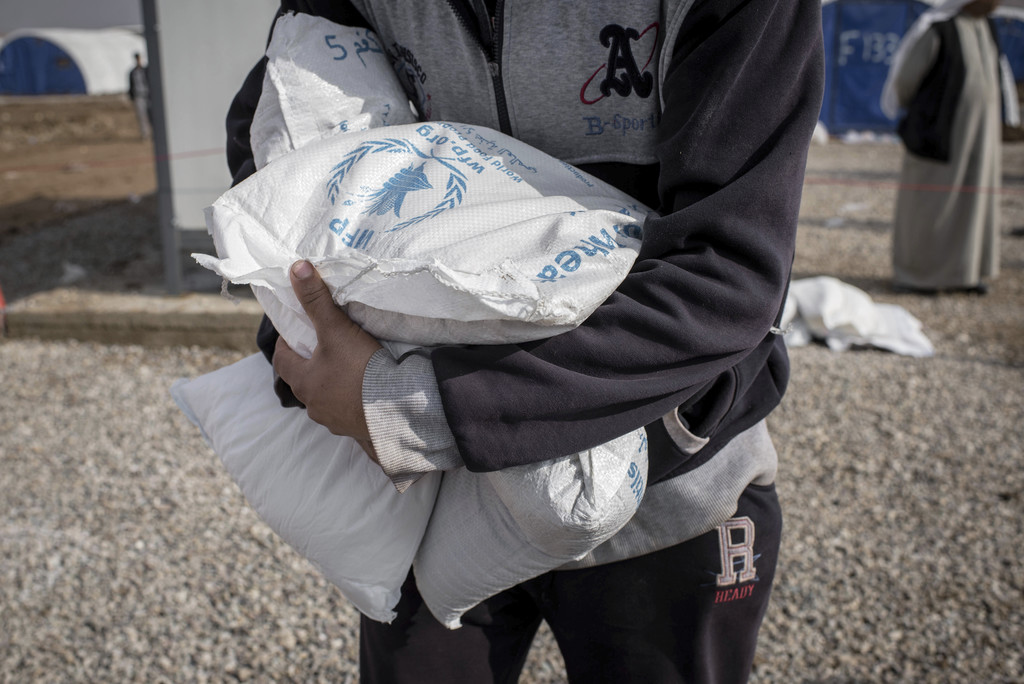 Food is distributed to displaced persons from Mosul at Sewdinan Camp for the displaced near Khazer, Iraq on Wednesday, Dec. 21, 2016. H...