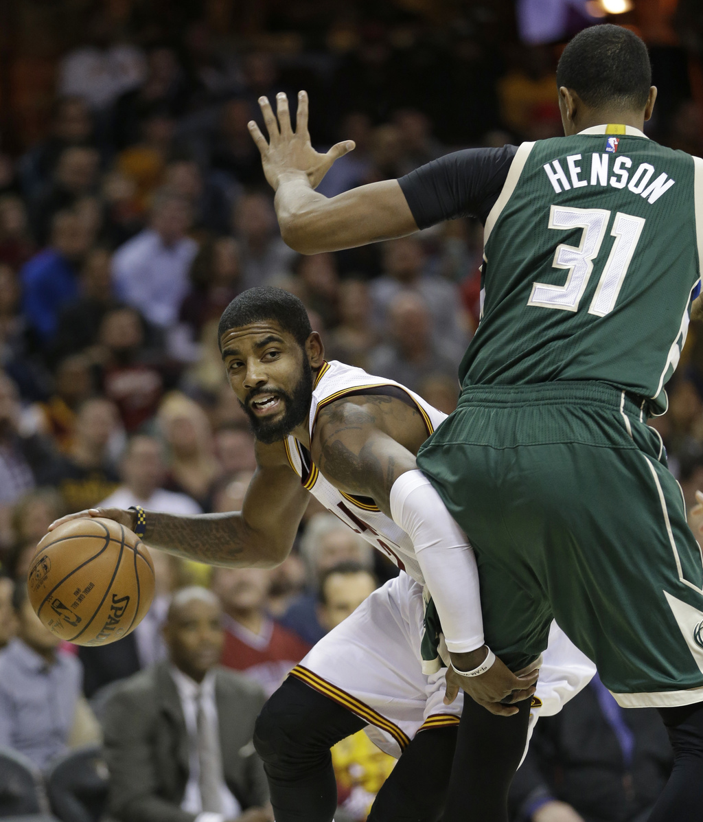Cleveland Cavaliers' Kyrie Irving (2) drives past Milwaukee Bucks' John Henson (31) during the first half of an NBA basketball game, We...