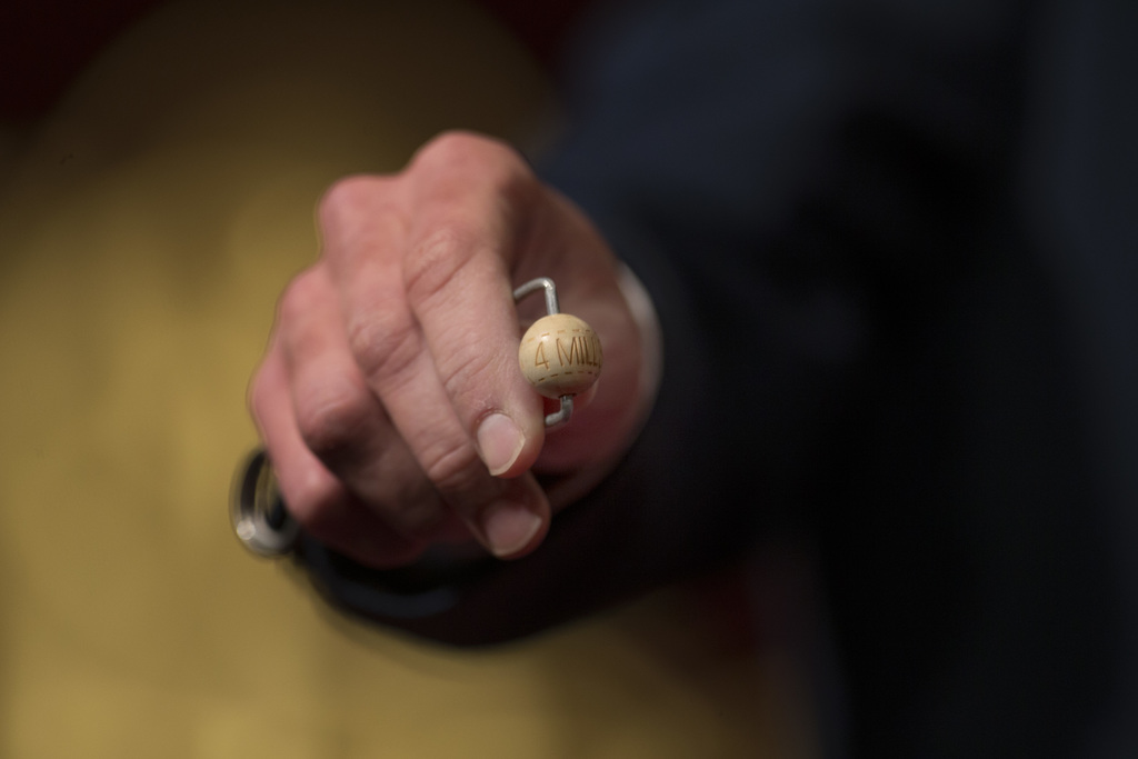 A worker holds out the ball with the top prize of euro 4,000,000 ($4,186,820) during the Spanish Christmas lottery draw, known as 'El G...