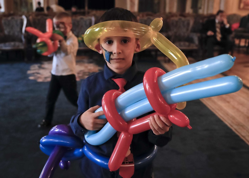 In this Tuesday, Dec. 13, 2016 photo, 6 year old Robert poses with balloons shaped to resemble a weapon during a Christmas show for chi...