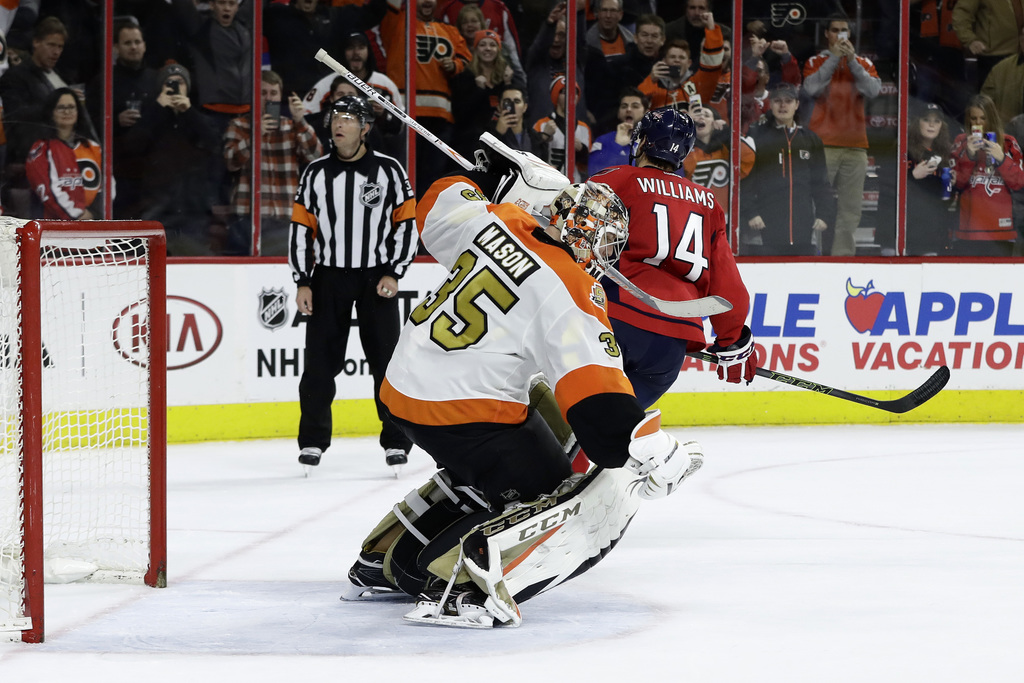 Philadelphia Flyers' Steve Mason, left, reacts after blocking a shot by Washington Capitals' Justin Williams during a shootout in an NH...