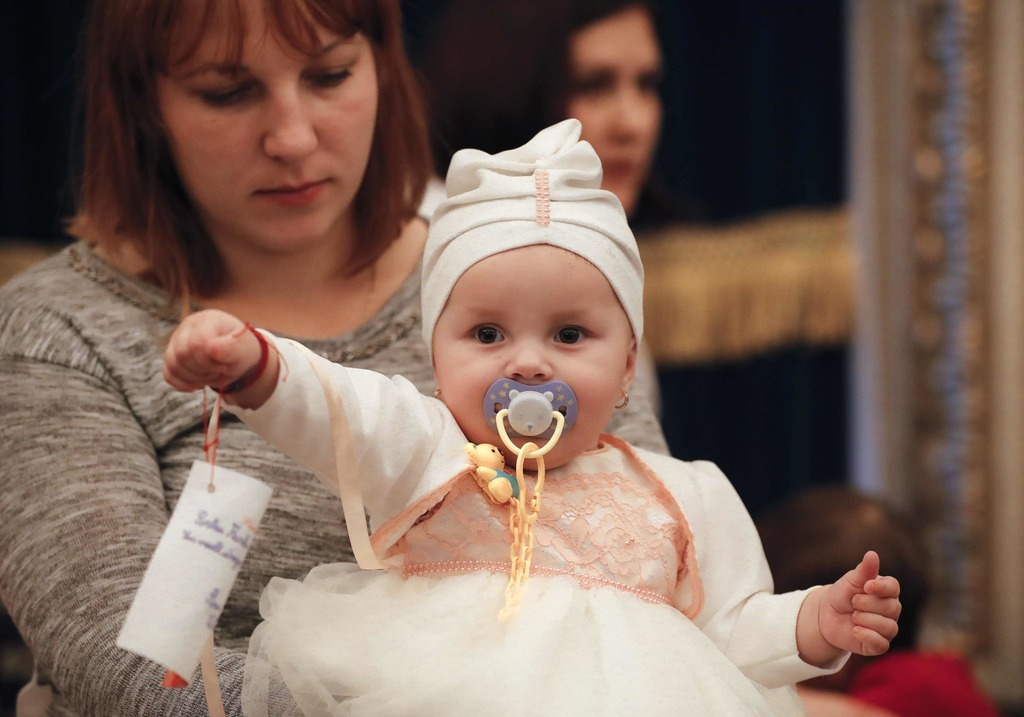 In this Tuesday, Dec. 13, 2016 photo, a woman holds a baby during a Christmas show for children of Romanian military families, in Bucha...