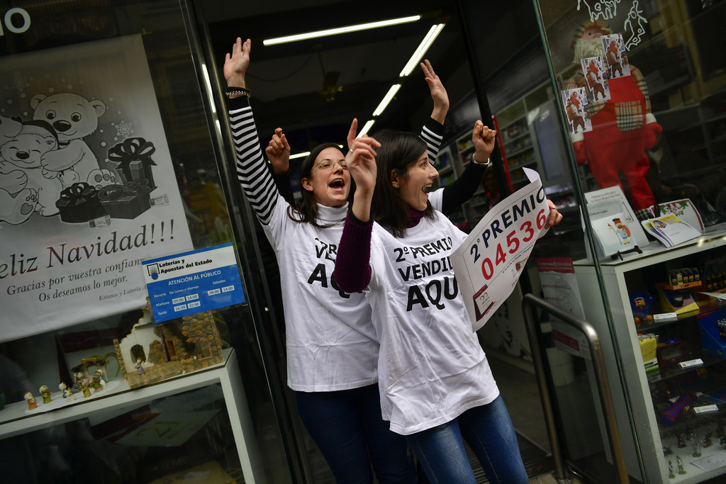 Monica, left, celebrates beside Ainoha in their lottery office after selling the second prize Christmas lottery ticket ''El Gordo'' wit...
