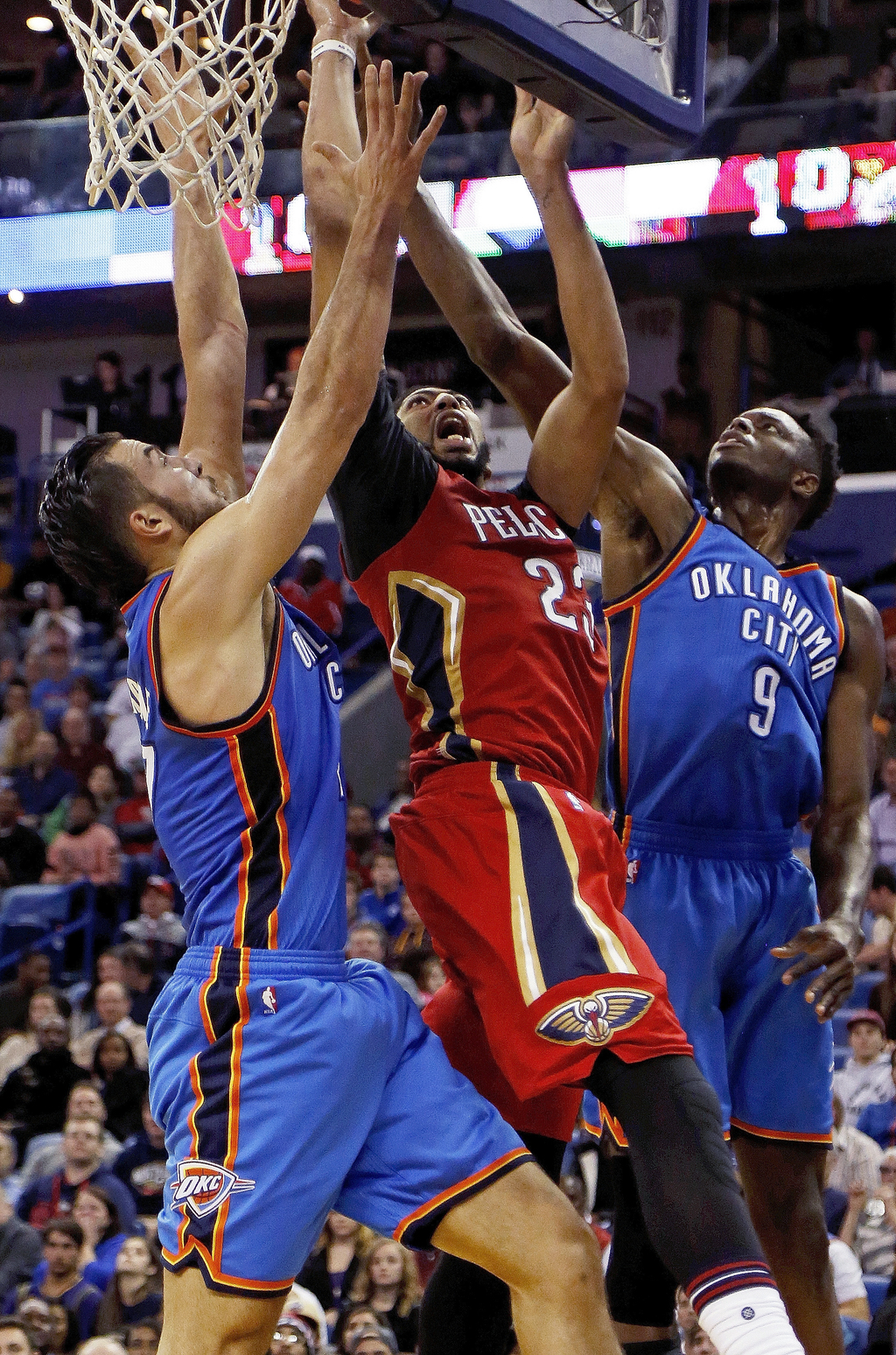 New Orleans Pelicans forward Anthony Davis, center, attempts to make a layup against Oklahoma City Thunder center Joffrey Lauvergne, le...
