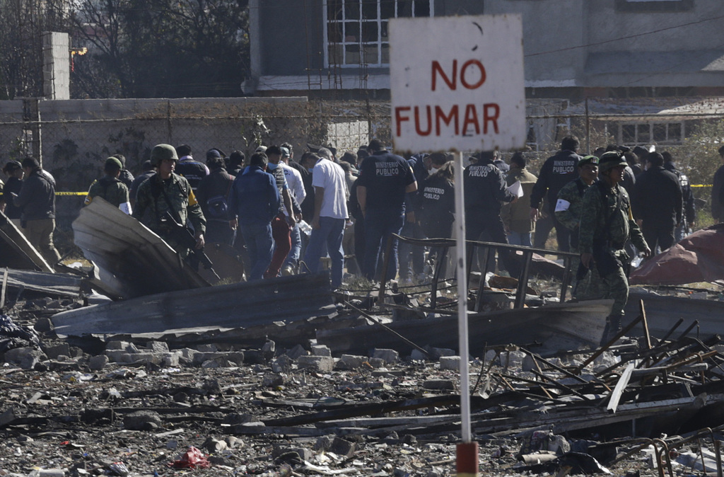 A no smoking sign stands above the scorched rubble of the open-air San Pablito fireworks market that exploded in Tultepec on the outski...