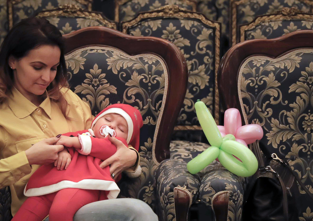 In this Tuesday, Dec. 13, 2016 photo, 19 month old Maya sleeps in her mother's arms after a Christmas show for children of Romanian mil...