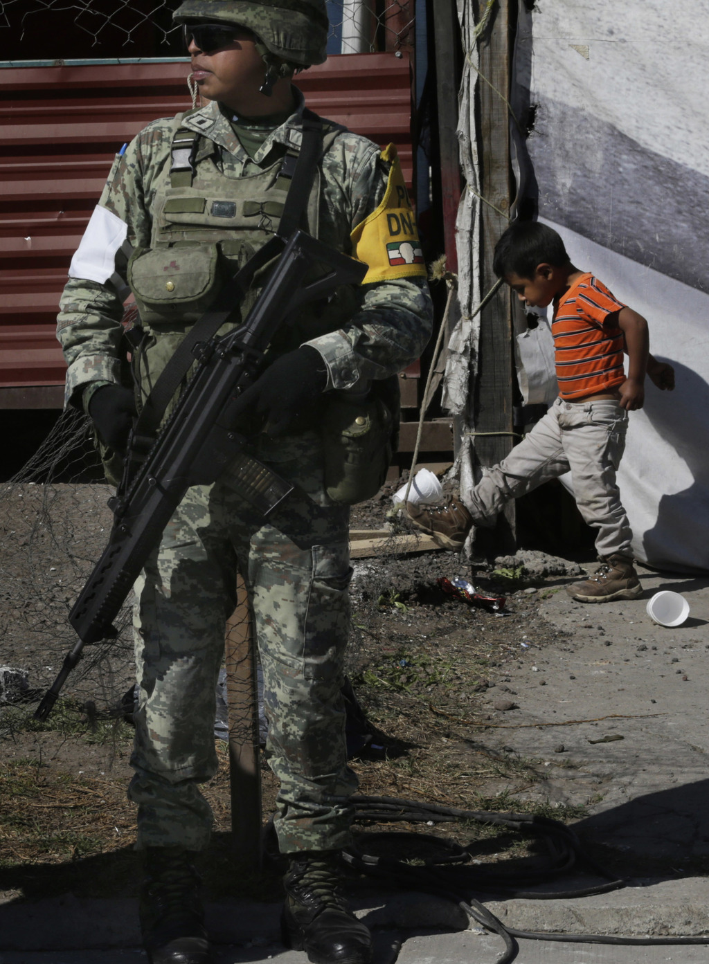A soldier stands guard as a child walks behind at the open-air San Pablito fireworks market that exploded  in Tultepec on the outskirts...