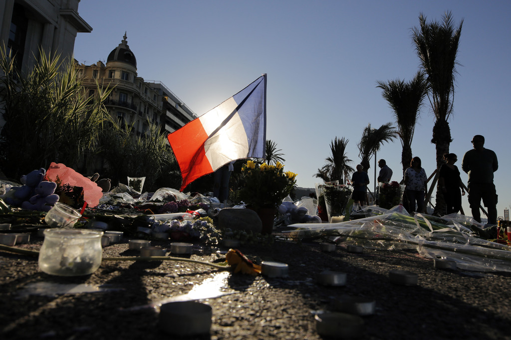 FILE - In this Sunday, July 17, 2016 file photo, a French flag stands among a floral tribute for the victims killed during a deadly att...