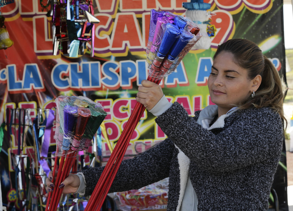 A woman looks at fireworks for sale a the Jaltenco Market in Zumpango, Mexico, Wednesday, Dec. 21, 2016.  On Tuesday, a larger firework...